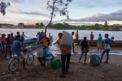 People wait on the Colombian side for a boat to bring them across to Venezuela.