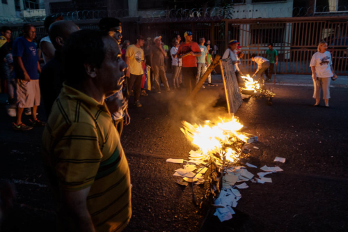 Some young men began to build barricades by setting fire to garbage and branches. Cars stopped. The drivers did not shout. They just turned around. At 6 pm, people at the crossroads sang the Venezuelan national anthem. They still loved their country.