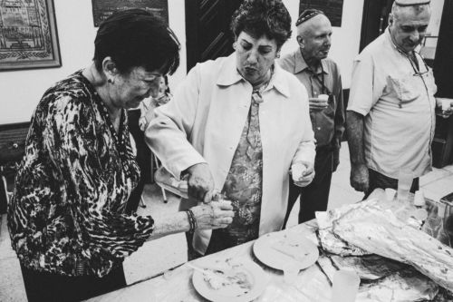Religion is not only about believing. It is also about being part of a community and supporting each other in a country in crisis. After each evening prayer, worshippers would share a meal and a drink in the synagogue. These women enjoyed the vodka blend prepared by Luttinger.