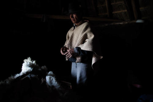 An indigenous guide stands inside his hut.